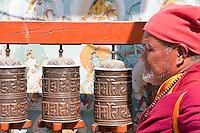 Bodhnath, Nepal.  Buddhist Monk Turning Prayer Wheel.