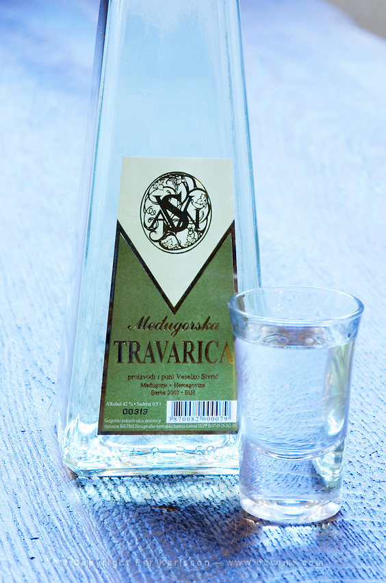 Triangular pyramid shaped Bottle of Travarica rakija grappa type grape spirit, a glass of digestif alcohol. In the restaurant and wine bar at the winery. Podrum Vinoteka Sivric winery, Citluk, near Mostar. Federation Bosne i Hercegovine. Bosnia Herzegovina, Europe.
