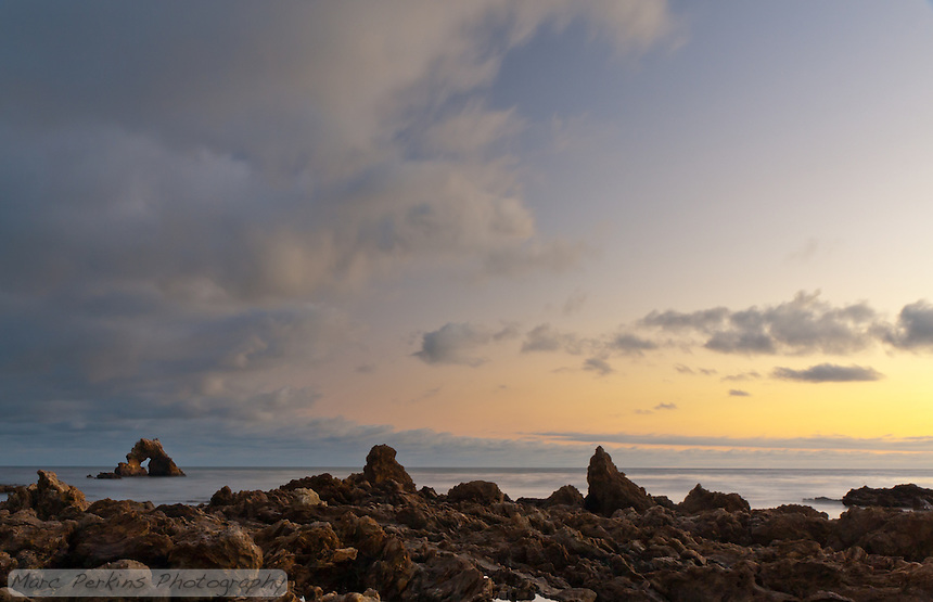 Sunset at Little Corona, focusing on the arch rock visible just off shore, with the rocky intertidal in the foreground and clouds drifting overhead.  This is a long exposure shot, so the ocean's water looks silky smooth.