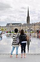 miror d'eau two young women st michel church place de la bourse bordeaux france