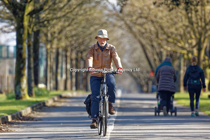 Pictured: A man cycles on the seaside path in Swansea, Wales, UK. Friday 27 March 2020<br /> Re: Covid-19 Coronavirus pandemic, UK.