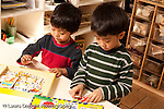 Preschool Headstart 3-5 year olds two boys working on puzzle showing word and object horizontal