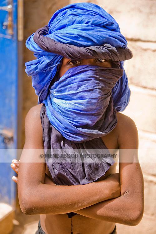 In Ouagadougou, Burkina Faso, Aljou Diallo, a young Fulani boy, wraps a turban around his head in traditional nomadic fashion.  The turban protects from the harsh dust and wind of the Harmattan season.