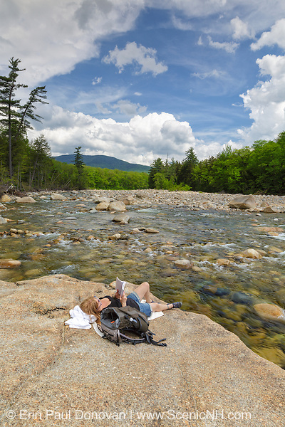 Woman reading a book on rock along the East Branch of the Pemigewasset River in Lincoln, New Hampshire USA during the spring months