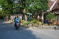 Yogyakarta, Java, Indonesia.  Family on a Motorbike Passing Newspaper on Display in a Residential Area.