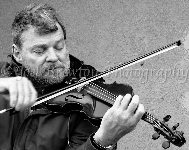 An aspiring musician serenades passers-by with his violin as he plays for handouts on the sidewalk.