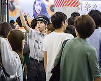 A station attendant is guiding passengers during a rush hour.
