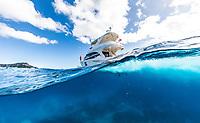 A woman enjoys the day aboard a power cruiser heading towards Diamond Head, Honolulu, O'ahu.