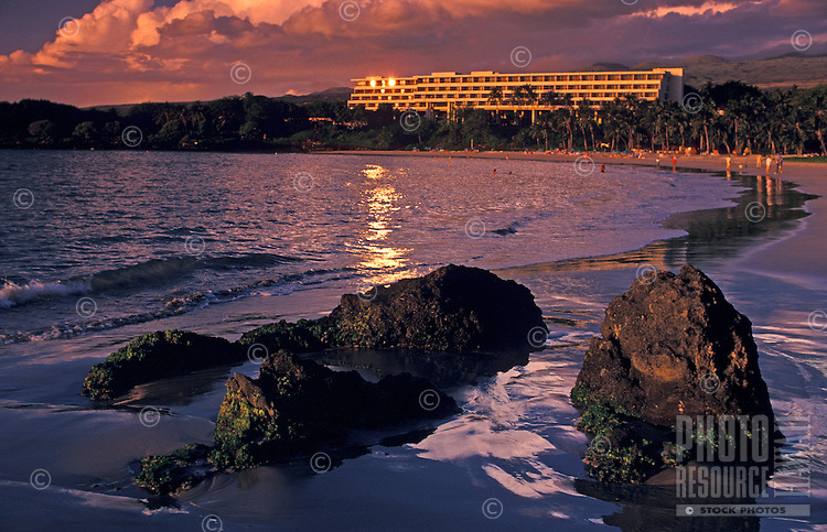 Group of large rocks on the beach near Mauna Kea beach hotel, Big Island, with people further along beach and setting sun glinting off hotel windows