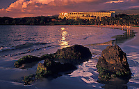 Group of large rocks on the beach near Mauna Kea beach hotel, Big Island, with people further along beach and setting sun glinting off hotel windows