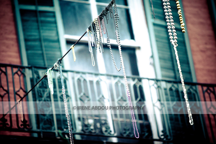 Mardi Gras beads hang on electrical and telephone wires, and residents' balconies throughout the French Quarter in New Orleans, Louisiana.  The beads are collected by residents each year, as they are thrown by krewes from parade floats.