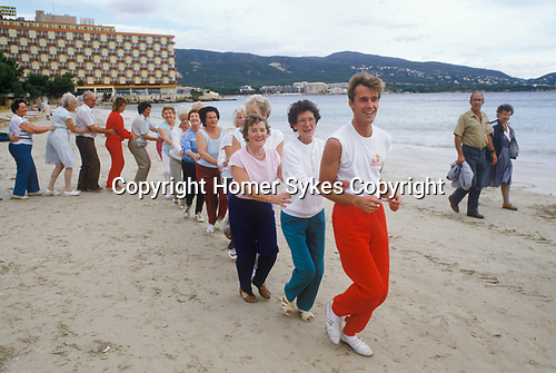 Young at Heart. British seniors on winter holiday in Balearic Islands Palma Nova Majorca Spain. Holiday rep leads the daily fun exercise class.