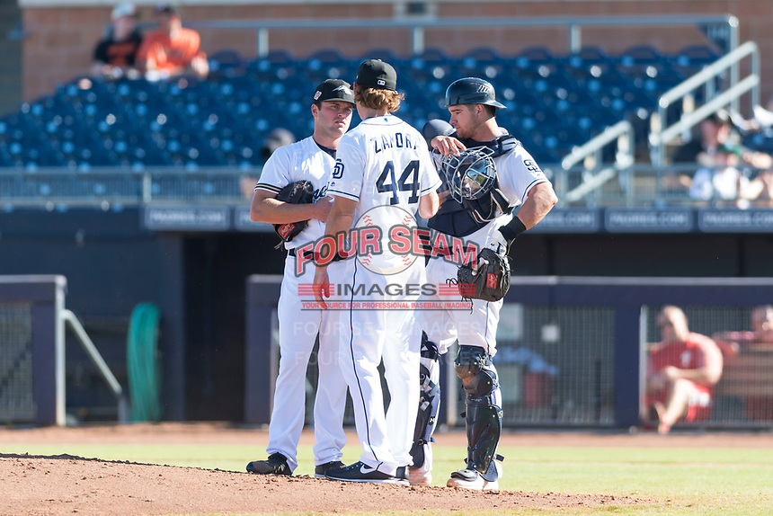 Peoria Javelinas relief pitcher Jon Olczak (29), of the Milwaukee Brewers organization, talks to pitching coach Pete Zamora (44) and catcher Austin Allen (24) during an Arizona Fall League game against the Scottsdale Scorpions at Peoria Sports Complex on October 18, 2018 in Peoria, Arizona. Scottsdale defeated Peoria 8-0. (Zachary Lucy/Four Seam Images)