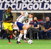 DALLAS, TX - JULY 25: James Sands #16 of the United States gains control of a loose ball in front of Cory Burke #9 of Jamaica during a game between Jamaica and USMNT at AT&T Stadium on July 25, 2021 in Dallas, Texas.