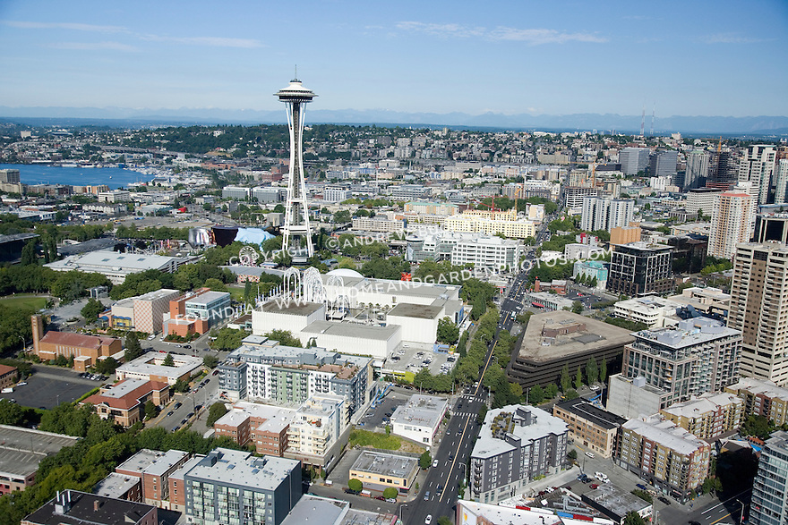 A sunny, summer afternoon aerial photo of Seattle, Washington's Belltown / Denny Triangle neighborhood showing the Space Needle, the tip of Lake Union in the back left, and the Cascade Mountains in the distance to the east.