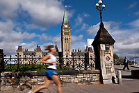 A woman runs by the Parliament in Ottawa Monday September 27, 2010. Parliament Hill (colloquially The Hill, in French: Colline du Parlement) is an area of Crown land on the southern banks of the Ottawa River in downtown with a Gothic revival suite of buildings, the parliament buildings, that serves as the home of the Parliament of Canada and contains a number of architectural elements of national symbolic importance.<br /> <br /> PHOTO :  Francis Vachon - Agence Quebec Presse