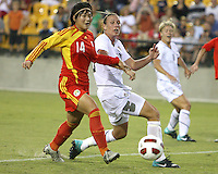 Abby Wambach #20 of the USA WNT slips the ball past Danyang Li #14 of the PRC WNT during an international friendly match at KSU Soccer Stadium, on October 2 2010 in Kennesaw, Georgia. USA won 2-1.