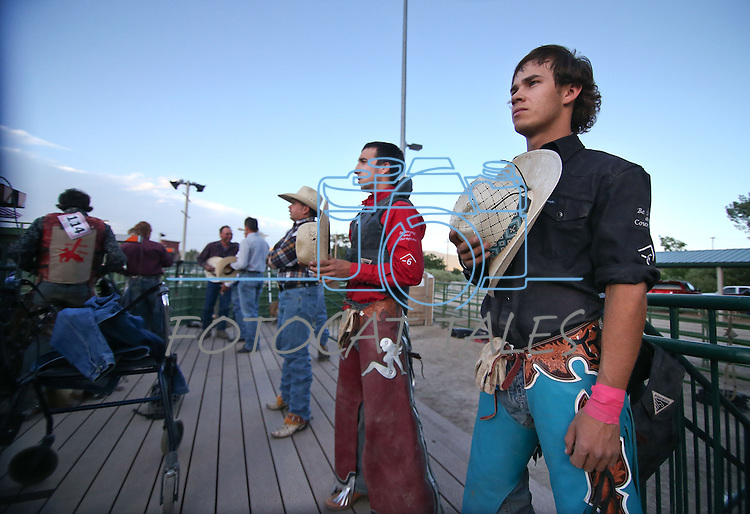 Amir Beardsley, in red, and Drew Culp, right, listen to the grand entrance ceremony at the Smackdown Tour Bull Riding event at Fuji Park in Carson City, Nev., on Saturday, June 7, 2014.<br /> Photo by Cathleen Allison