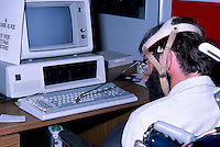 Disabled Man using a Specially Fitted Head Attachment, with Pointing Device, to type on Computer Keyboard