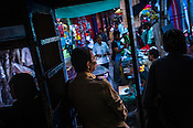 A ticket collector, centre, looks on as passengers are silhouetted on a Calcutta Tram in Kolkata, West Bengal, India,
