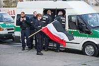 """Ca. 50 Neonazis der NPD, der Neonazi-Partei """"Die Rechte"""" und Hooligans protestierten am 20. April 2015 in Berlin Marzahn-Hellersdorf gegen eine geplante Fluechtlingsunterkunft. Die Neonazis wollten ein """"Geburtstagsstaendchen"""" anlaesslich des Hitlergeburtstages (20. April) singen, dies wurde ihnen von der Polizei jedoch untersagt.<br /> Im Bild: Polizeibeamte beschlagnahmen schwarz-weiß-rote Fahnen von Neonazis.<br /> 20.4.2015, Berlin<br /> Copyright: Christian-Ditsch.de<br /> [Inhaltsveraendernde Manipulation des Fotos nur nach ausdruecklicher Genehmigung des Fotografen. Vereinbarungen ueber Abtretung von Persoenlichkeitsrechten/Model Release der abgebildeten Person/Personen liegen nicht vor. NO MODEL RELEASE! Nur fuer Redaktionelle Zwecke. Don't publish without copyright Christian-Ditsch.de, Veroeffentlichung nur mit Fotografennennung, sowie gegen Honorar, MwSt. und Beleg. Konto: I N G - D i B a, IBAN DE58500105175400192269, BIC INGDDEFFXXX, Kontakt: post@christian-ditsch.de<br /> Bei der Bearbeitung der Dateiinformationen darf die Urheberkennzeichnung in den EXIF- und  IPTC-Daten nicht entfernt werden, diese sind in digitalen Medien nach §95c UrhG rechtlich geschuetzt. Der Urhebervermerk wird gemaess §13 UrhG verlangt.]"""
