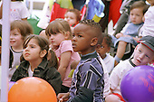 Children watch a storyteller at a Healthy Living Day organised by Camden Sure Start.