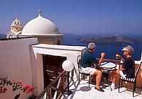 A senior couple enjoys a meal on a balcony overlooking the Mediterranean Sea. Santorini, Greece.