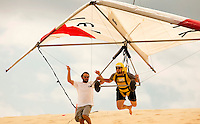 Adventure travelers learn to hang glide off the sand dunes at Jockey's Ridge State Park in NC's Outer Banks. The popular air sport attracts individuals who want to soar and glide over the sandy beach. People new to the sport can learn at such hang glide schools as the Kitty Hawk Kites' Hang Gliding Training Center, one of the largest hang gliding school in the world. Persons with USHGA Hang 1 or other agency-approved rating cards may hang glide on the ridge as well.