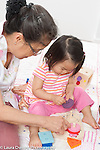 18 month old toddler girl with grandmother, playing with wooden peg puzzle listening as grandmother shows her where to put the piece