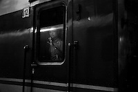 A woman looks out of a train car in Shanghai, China.