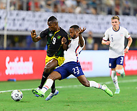 DALLAS, TX - JULY 25: Kellyn Acosta #23 of the United States and Cory Burke #9 of Jamaica battle for control of the ball during a game between Jamaica and USMNT at AT&T Stadium on July 25, 2021 in Dallas, Texas.
