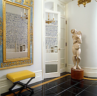 The apartment houses a stunning collection of antique furniture and works of art such as this ornate mirror and modernist sculpture flanking mirrored double doors in the entrance hall