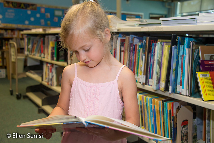 MR / Schenectady, NY. Zoller Elementary School (urban public school). Kindergarten classroom. Girl (5) looks at book in school library. MR: Bog2. ID: AM-gKw. © Ellen B. Senisi.