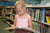 MR / Schenectady, NY. Zoller Elementary School (urban public school). Kindergarten classroom. Girl (5) looks at book in school library. MR: Bog2. ID: AM-gKw. © Ellen B. Senisi.