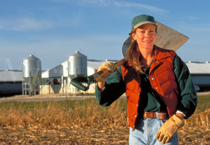 A female farmer poses before a midwest hog-confinement business.