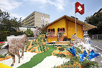 Switzerland. Canton of Neuchâtel. Neuchâtel. Grape Harvest Festival. The flower parade (corso) with its creative vehicles. A chalet, a swiss flag and some goats. © 2006 Didier Ruef