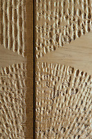 A detail of the pattern carved on the doors of the natural oak cupboard in the bedroom