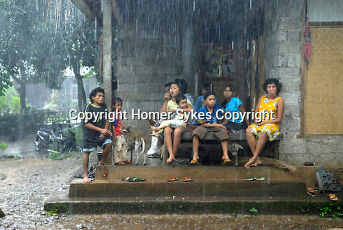 Women wait for the cock fight to be over. Heavy rain. Bali cock fighting Indonesia  Group of men in rural community gambling of cockerel fighting match. Lovina. Island of Bali 2000s.