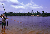Tataquara, Amazon, Brazil. Boy fishing in the Xingu River with bow and a long arrow.