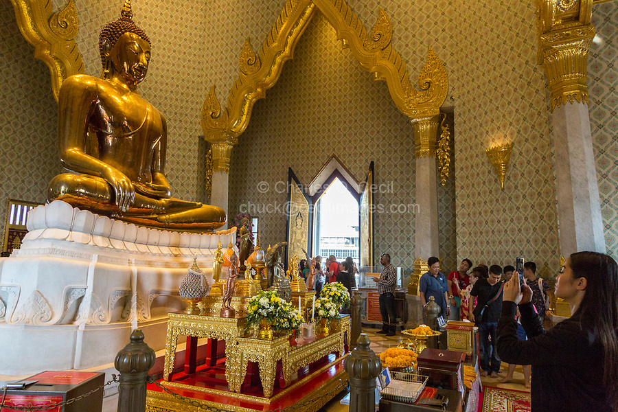 Bangkok, Thailand.  Worshipers Mingle with Tourists at the Wat Traimit, Temple of the Golden Buddha.  The Buddha sits in the Bhumisparsha gesture, calling the earth to witness.
