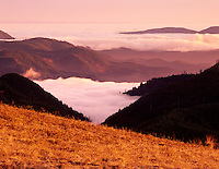 Sunset view with fog in valleys of Siuslaw National Forest. As seen from Mary's Peak, Oregon.