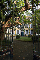 Original wrought-iron gates open onto a shady courtyard approach to the restored 18th century house