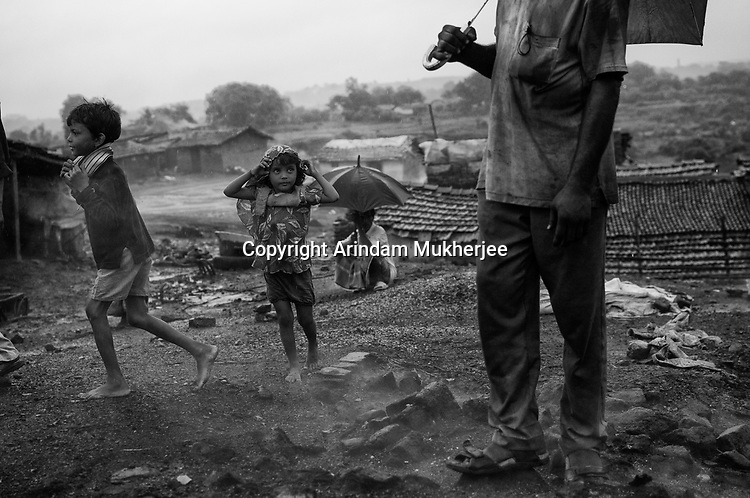 Children are playing barefoot on the ground as the mine fire rages just beneath the surface. As a result, their legs get burn wounds.A huge coal mine fire is engulfing the city of Jharia from all its sides. All scientific efforts have gone in vain to stop this raging fire. This fire is affecting lives of people living in and around Jharia. Jharkhand, India. Arindam Mukherjee
