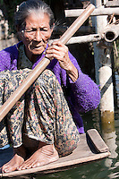 Myanmar, Burma.  Old Intha Woman Paddling her Boat, Inle Lake, Shan State.