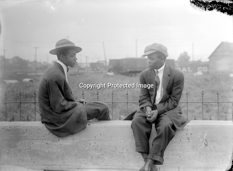 """Note: Also image LB184<br /> DAKOTA TALBERT AND FRIEND. Dakota Talbert was born in Fort Scott, Kansas, and came to Lincoln with his family in 1913. He served in the army in France during World War I. His uniform featured a hat very much like this one. The concrete wall was at the west end of the viaduct that carried O Street—Lincoln's """"Main Street""""—over the railyard on the west side of downtown. His sister identified the young man seated with Talbert as most likely his friend Vernon Howard. Talbert worked as an elevator operator, shoe shiner, driver, and cook in Lincoln and Omaha restaurants.<br /> <br /> Photographs taken on black and white glass negatives by African American photographer(s) John Johnson and Earl McWilliams from 1910 to 1925 in Lincoln, Nebraska. Douglas Keister has 280 5x7 glass negatives taken by these photographers. Larger scans available on request."""