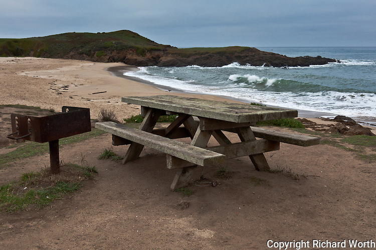 A rustic picnic table and barbecue with a view of ocean waves at a public beach south of San Francisco on California's coast.