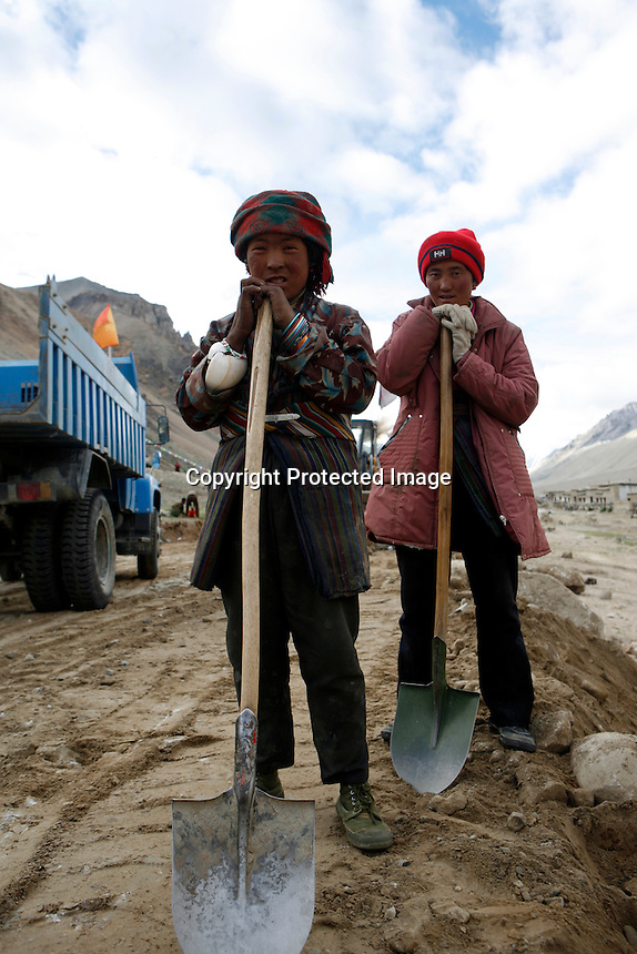"China started building a controversial 67-mile ""paved highway fenced with undulating guardrails"" to Mount Qomolangma, known in the west as Mount Everest, to help facilitate next year's Olympic Games torch relay./// Two young women work with a shovels building the road to Everest Base Camp.<br /> Tibet, China<br /> July, 2007"