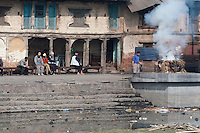 Pashupatinath, Nepal.  A Family Member Oversees a Cremation on a Ghat on the Banks of the Bagmati River, adjacent to Nepal's Most Important Hindu Temple.