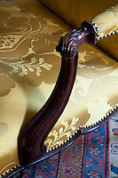 Detail of the carved arm on a Chippendale chair, newly covered in silk damask