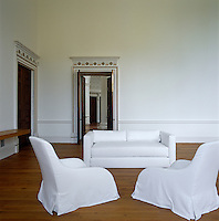 The main reception room with Italian armchairs in white loose covers and a rectangular sofa designed by Nigel Tuersley